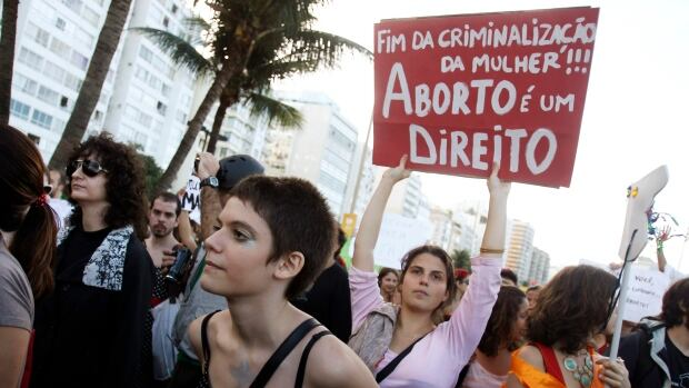 Abortion is currently illegal in Brazil except in a few extreme circumstances. In this July 27, 2013 photo, people protest at a pro-choice rally in Rio de Janeiro. The sign reads 'No more criminalization of women, abortion is a right.'