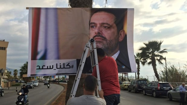 Workers hang a poster of former prime minister Saad Hariri with Arabic words that read, 'We are all Saad,' on a seaside street in Beirut on Thursday.
