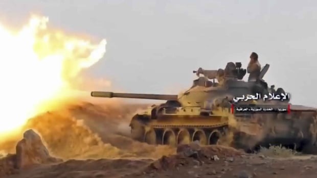 This frame grab from video provided Wednesday by the government-controlled Syrian Central Military Media shows a tank firing on militants' positions on the Iraq-Syria border. The Britain-based Syrian Observatory for Human Rights said Islamic State militants have withdrawn from their last stronghold.