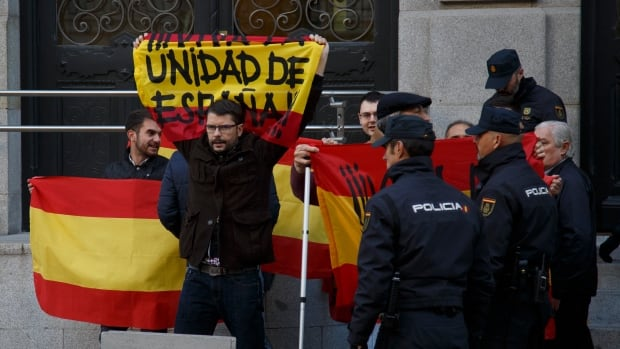 Pro-unity protesters hold Spanish flags reading 'For the unity of Spain' as Catalan regional parliament speaker Carme Forcadell arrives at the country's supreme court on Thursday in Madrid.