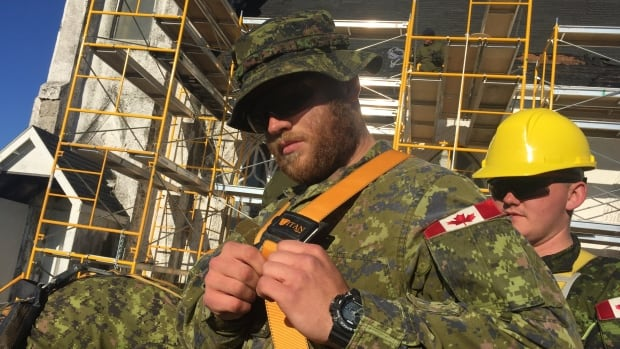 Sapper Earl Fleming straps on a harness before ascending the scaffolding.