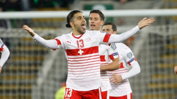 Switzerland's Ricardo Rodriguez, centre, celebrates after scoring from the penalty spot during the World Cup qualifying playoff, the only goal in their 1-0 win over Northern Ireland.