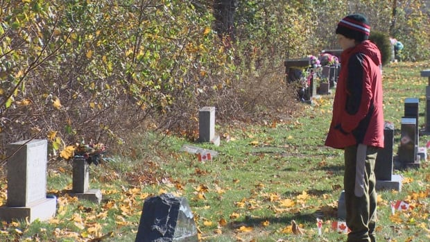 A student from Harold Peterson Middle School in Oromocto looks at a headstone while taking part in the No Stone Left Alone program.