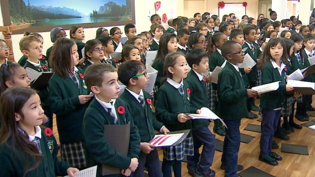 Students from Dr. J.K. Mulloy elementary school in northwest Calgary sing to residents at Colonel Belcher retirement home. The students also presented poppies they had grown.