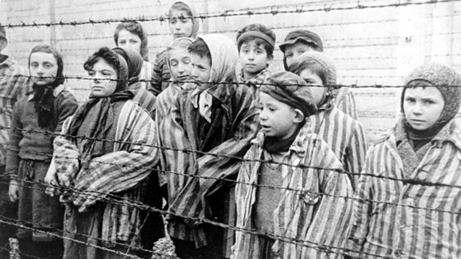 Child survivors of Auschwitz, wearing adult-size prisoner jackets, stand behind a barbed wire fence. Miriam Ziegler (far-left corner) was nine-years-old when Auschwitz and Birkenau were liberated in January, 1945. She is now 82-years-old and lives in Toronto.
