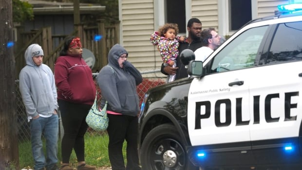 People begin to gather as officers investigate the scene a shooting, Thursday, Nov. 9, 2017, in Kalamazoo, Mich. Police said three people were shot, including two fatally, at a home in southwestern Michigan following what was described as a family disturbance.