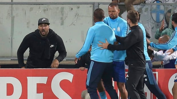 Marseille's Patrice Evra, centre left, is led away by his teammate Rolando after a scuffle with Marseille supporters who trespassed into the field before a Europa League soccer match in Guimaraes, Portugal on Nov. 2.