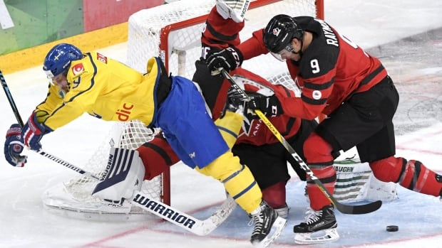 Canada goalie Ben Scrivens gets caught up in the melee as teammate Mason Raymond clears Sweden's Robert Nilsson from the crease during Canada's 2-0 loss at the Karjala Cup on Friday.