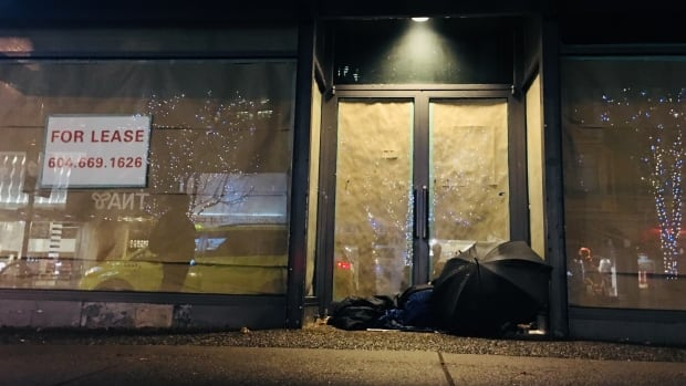A man sleeps in the doorway of an unrented store on Robson Street in downtown Vancouver.