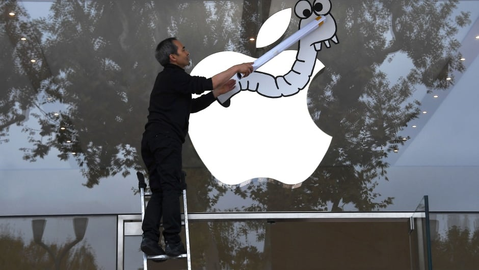 An activist from the Association for the Taxation of financial Transactions and Citizen's Action (ATTAC) sticks a poster on the window of the Apple store during a protest in southern France.