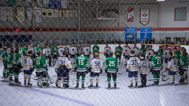 The Renfrew Timberwolves and Alexandria Glens form a circle around Alex Paquette and Brandon Hanniman's team numbers, stencilled beneath the ice, as their jerseys are raised to the rafters. Paquette and Hanniman both died as the result of a single-car accident that occurred on Oct. 27, 2017.