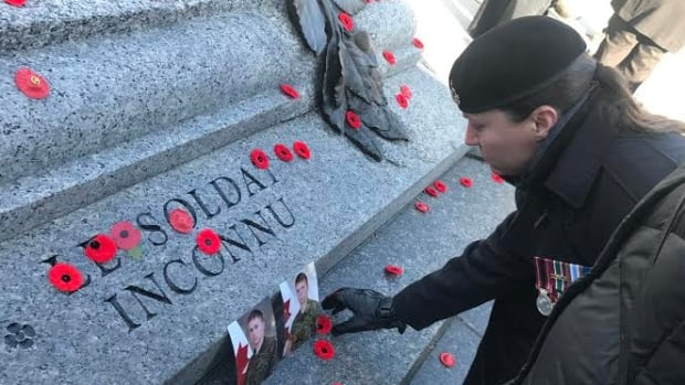 Natacha Dupuis, a retired master corporal, lays photos of troopers Jack Bouthillier and Corey Hayes on the tomb of the Unknown Soldier in Ottawa. The two were killed in Afghanistan in 2009, where Dupuis also served.