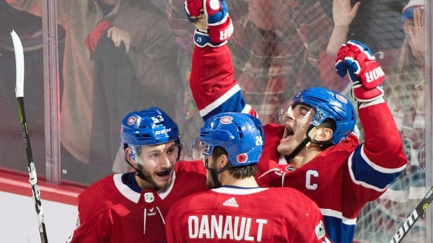 Max Pacioretty, right, of Canadiens celebrates his game-winning OT goal with teammates Victor Mete and Phillip Danault to help Montreal defeat the Buffalo Sabres 2-1 on Saturday.
