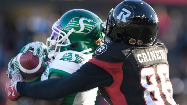 Saskatchewan Roughriders' Jovon Johnson (1) makes an interception against Ottawa Redblacks' Juron Criner (86) during second half Eastern semifinal CFL action in Ottawa on Sunday, Nov. 12, 2017.
