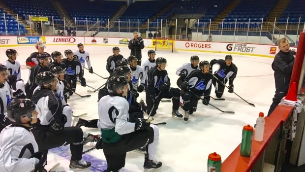 Team QMJHL assistant coach Darren Rumble goes over the game plan for Tuesday's game against Team Russia, while Islanders head coach and general manager Jim Hulton, who will serve as an assistant coach, looks on.