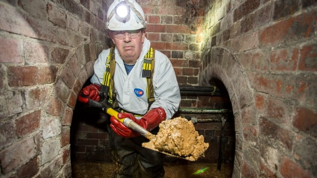 Vince Minney, a Thames Water sewer flusher, scoops out a chunk of the Chinatown fatberg.