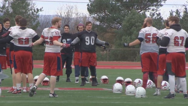 The Acadia Axemen practise on their home field on Monday.