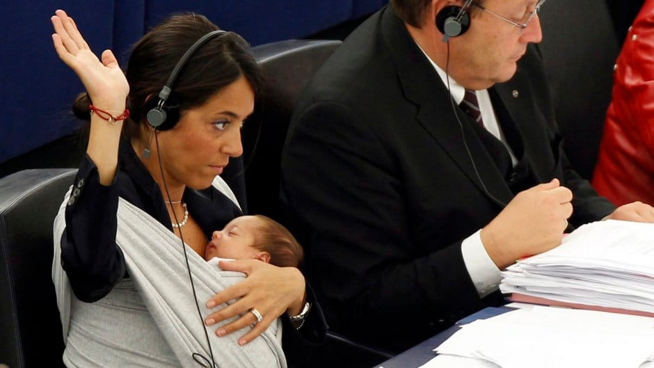 Italian Member of the European Parliament Licia Ronzulli, left, takes part in a vote as she cradles her baby at the European Parliament in Strasbourg, France.