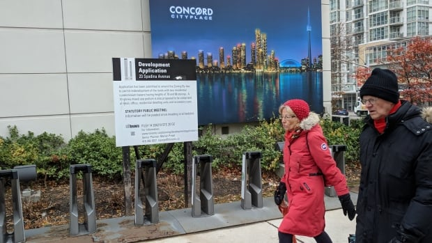 People walk past a notification about two proposed condo towers in Toronto.