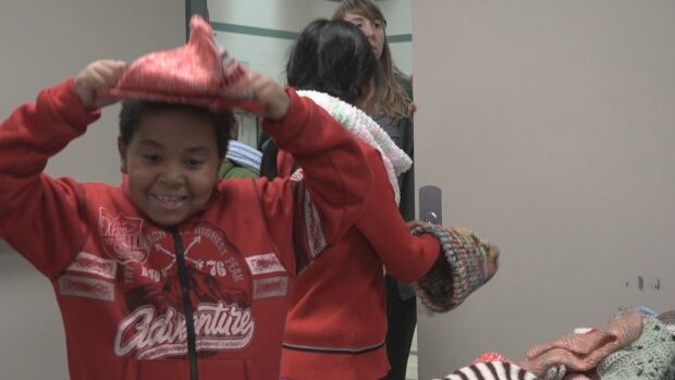 Kids from the Sister MacNamara Boys and Girls Club try out new knitwear donated by the Winnipeg Art Gallery's Crafted Show and Sale.