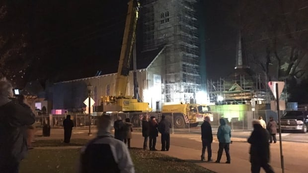 A crowd gathered at 6 a.m. Tuesday morning to watch as a giant crane lifted St. Anne's refurbished steeple atop its tower.