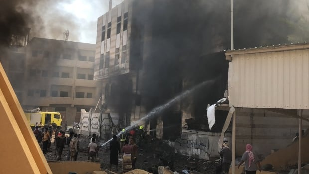 Yemeni firefighters douse flames following a deadly explosion near a security post in the southern port city of Aden, which ISIS took credit for.