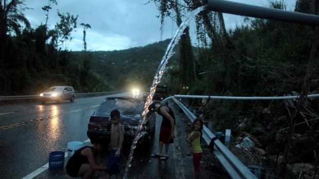 A family bathe and wash their car with mountain spring water in Utuado, Puerto Rico, on Nov. 9. Many residents are still without running water and electricity after Hurricane Maria made landfall in September.
