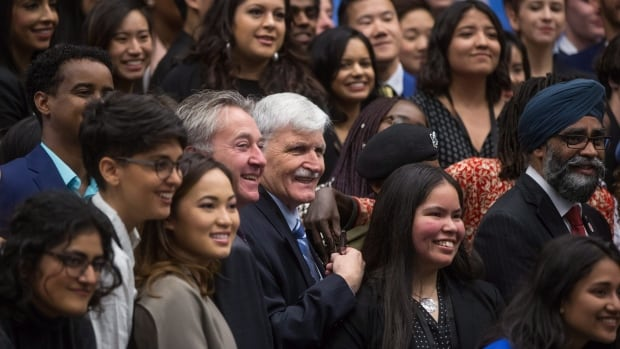 Retired lieutenant-general Romeo Dallaire, centre, and Defence Minister Harjit Sajjan, far right, pose for a photograph with youth representatives during a youth as peace builders working session at the 2017 United Nations Peacekeeping Defence Ministerial conference in Vancouver, B.C., on Nov.