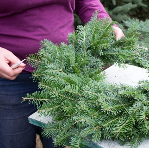attaching bunches of greens to wreath form