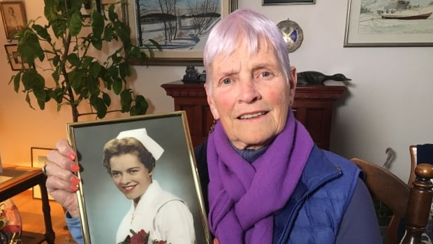 Janet Sims, 80, holds a picture of herself taken when she was a young nurse.
