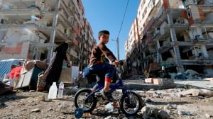Iran earthquake Iranian boy rides a bicycle through the rubble