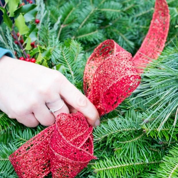 Adding bow to wreath