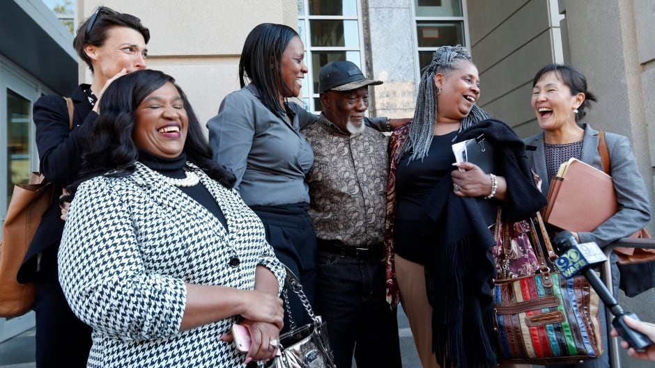 Family members of Wilbert Jones, flanked by attorneys from Innocence Project New Orleans, speak on the steps of state district court in Baton Rouge, La.