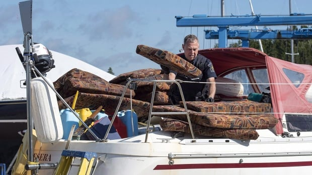 A Canada Border Services Agency officer inspects the sailboat Quesera at East River Marine in Hubbards, N.S., on Friday, Sept. 8, 2017.