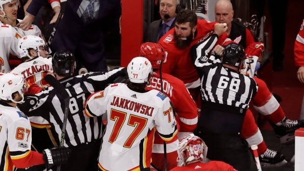 Luke Witkowski, top right, is held back by lineman Scott Driscoll during a brawl on Wednesday. Witkowski will now serve a 10-game suspension for leaving the bench to fight.