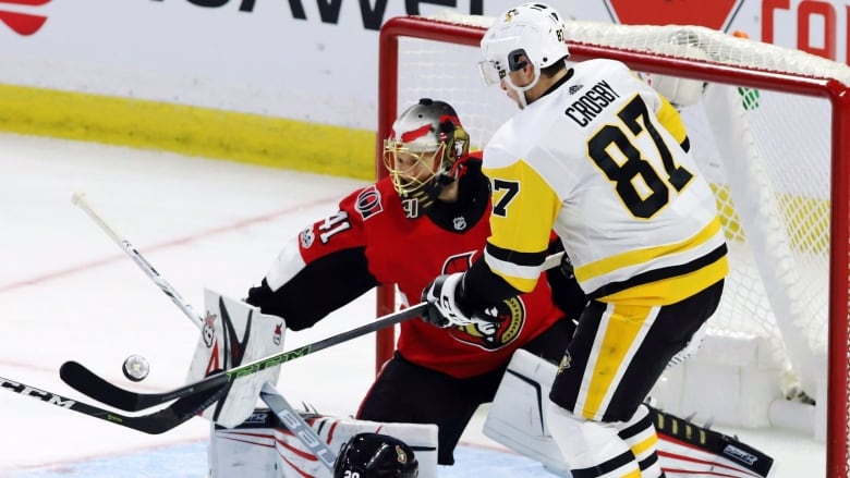 Sidney Crosby of the Penguins tries to tip the puck in front of Ottawa  Senators' goalie Craig Anderson during Pittsburgh's 3-1 win on Thursday.