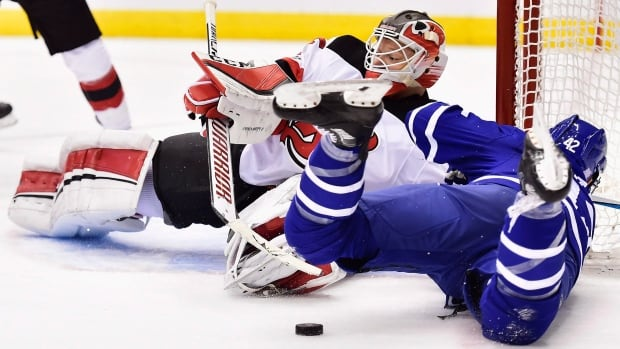 Toronto's Tyler Bozak stumbles as New Jersey goalie Cory Schneider makes the save in the Leafs' 1-0 overtime win Thursday.
