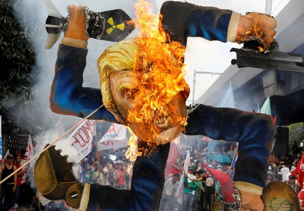 ASEAN SUMMIT Protesters burn an effigy of Donald Trump