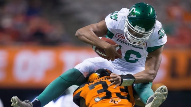 Saskatchewan Roughriders' quarterback Brandon Bridge, top, leaps over the B.C. Lions' Tevin McDonald while running with the ball during the second half of a pre-season CFL game in Vancouver, B.C., on Friday, June 16, 2017.
