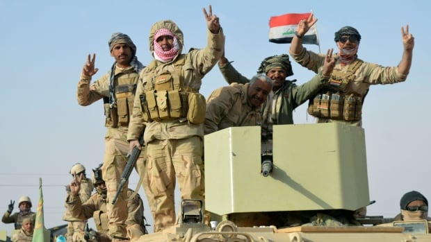 Iraqi forces flash the victory sign after they captured Rawa, the last remaining town under ISIS control, in Iraq on Friday.