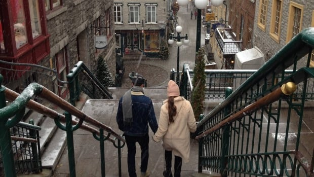 A couple walk together during the first snowfall of the season in Quebec City.