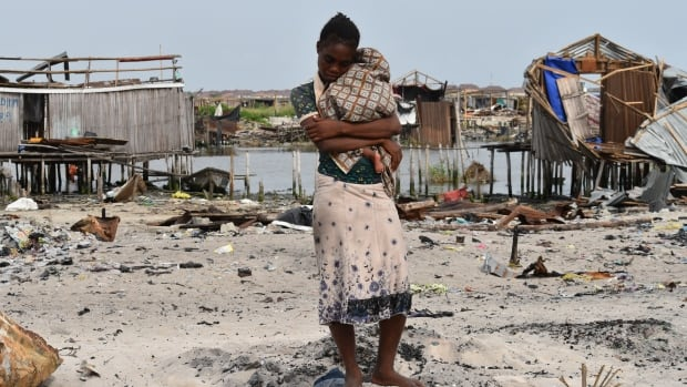 Florence Keyimo, 27, cradles her baby on the spot where her home used to be in Otodo-Gbame, a waterfront community in Lagos, Nigeria.