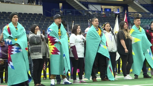 The Thompson brothers are draped in blankets, in place of traditional buffalo robes—a gift given to them by the Saskatoon Tribal Council.