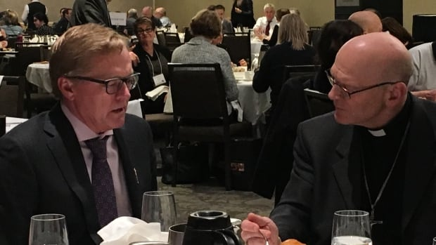 Alberta Education Minister David Eggen (left) talks with a reverend over lunch at the Alberta Catholic School Trustees' Association's annual general meeting on Saturday.