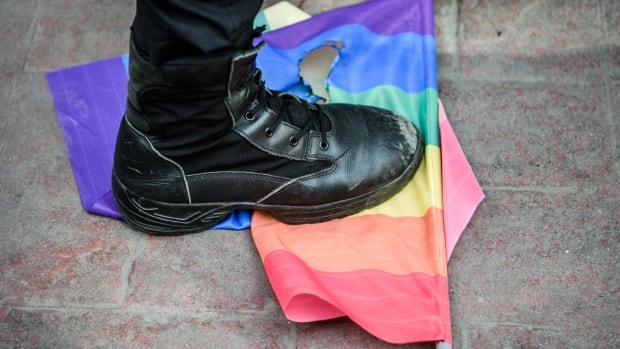 A Turkish anti-riot police officer steps on a rainbow flag during a rally staged by the LGBT community in Istanbul in June 2016.