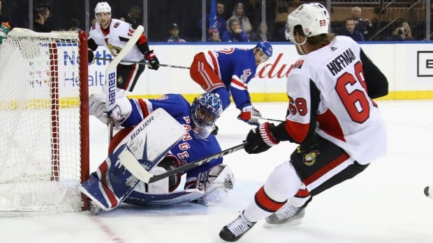 Henrik Lundqvist of the New York Rangers makes a save as Mike Hoffman of the Ottawa Senators looks for a rebound.