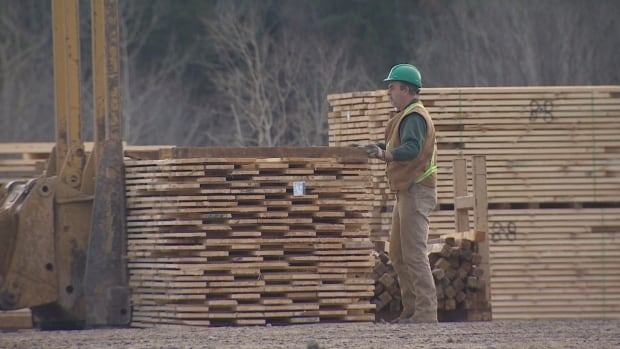 An employee stacks boards at the J.D. Irving sawmill in Doaktown on Monday. The mill, built in the 1950s, is running at full employment and full capacity.
