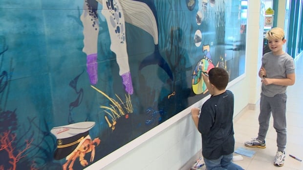 Grade 5 students Sam Crowley and Tyler Brooks enjoyed colouring-in the submarine on the new interactive ceramic tile mural in the lobby of Seaside Park Elementary School.