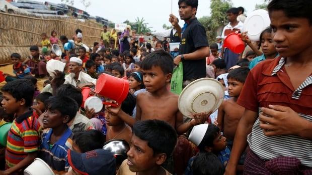 Rohingya refugee children wait to receive food outside the distribution center at Palong Khali refugee camp near Cox's Bazar, Bangladesh.