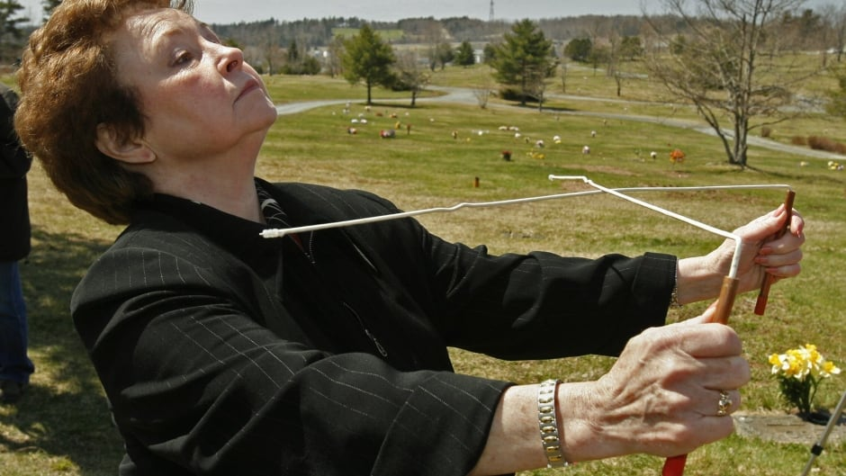A member of the Buctah Dancers on the 1960s television show Don Messer's Jubilee holds divining rods attempting to contact the late Don Messer at the Canadian fiddling icon's grave in Nova Scotia.